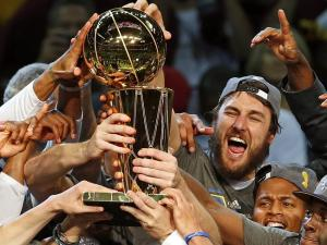 Andrew Bogut celebrating with the Larry O'Brien trophy as NBA Champion.