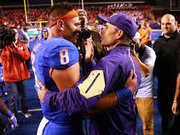Washington coach Chris Petersen embraces a former player.